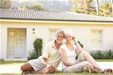 Senior Couple sitting Outside Dream Home