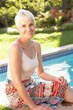 Senior Woman Relaxing By Pool In Garden