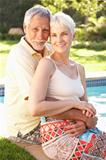 Senior Couple Relaxing By Pool In Garden