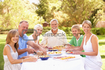 Extended Family Enjoying Meal In Garden