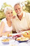 Senior Couple Enjoying Meal In Garden