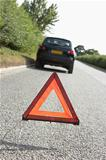 Car Broken Down On Country Road With Hazard Warning Sign In Foreground