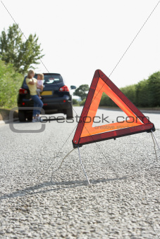 Mother And Daughter Broken Down On Country Road With Hazard Warning Sign In Foreground