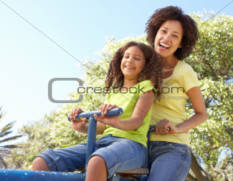 Mother And Daughter Riding On Seesaw In Park