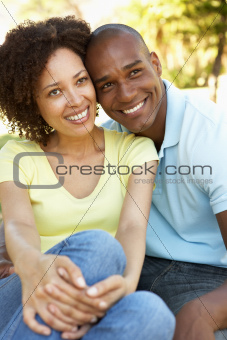 Portrait Of Young Couple Sitting In Park