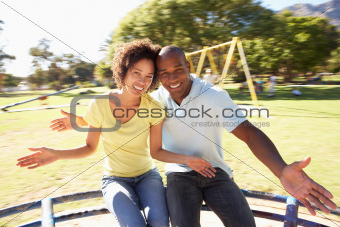 Young Couple Riding On Roundabout In Park