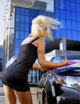 blonde businesswoman writing something
