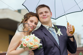 bride and groom under a white umbrella
