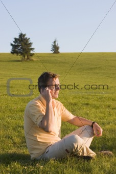 Man with cell phone in a meadow