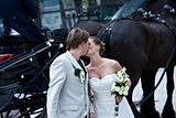 bride and groom kissing in front of coach