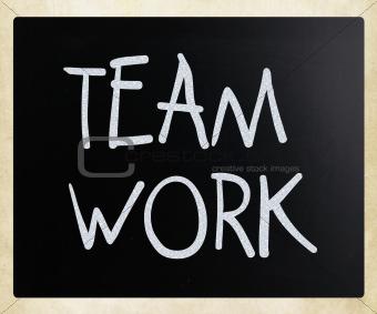 """""""Teamwork"""" handwritten with white chalk on a blackboard"""