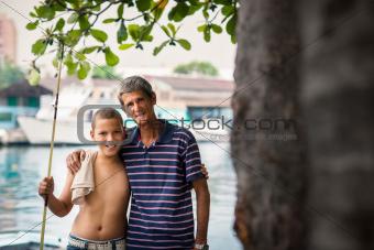 Happy family portrait of boy and grandpa hugging