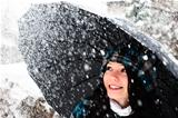 Young woman with umbrella in a blizzard