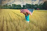girl in wheat field with flag