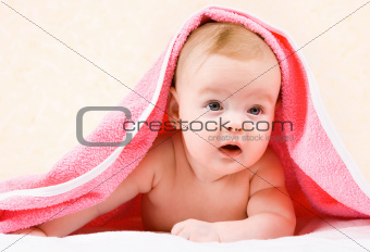 baby looking out from under blanket
