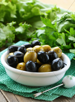 appetizer black and green olives  on a wooden table