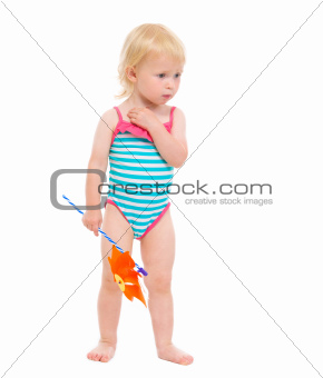 Thoughtful baby in swimsuit with pinwheel