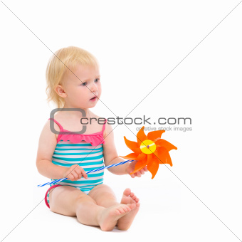 Thoughtful baby in swimsuit with pinwheel sitting on floor