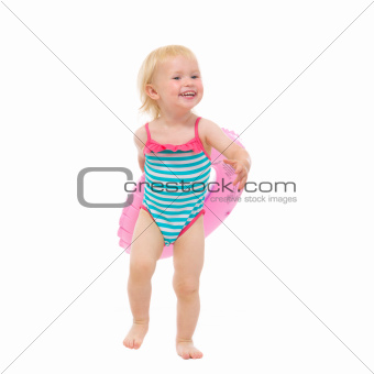 Smiling baby in swimsuit with inflatable ring
