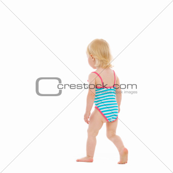 Baby in swimsuit walking away. Rear view
