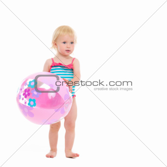 Baby in swimsuit with inflatable beach ball
