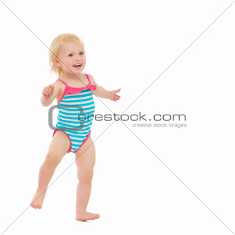 Smiling baby in swimsuit dancing