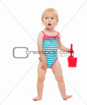 Surprised baby in swimsuit playing with bucket and shovel