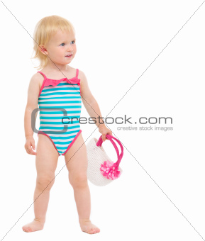 Cute baby in swimsuit with handbag looking on copy space