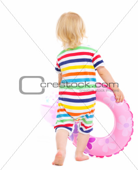 Baby in swimsuit playing with inflatable ring and beach ball. Rear view