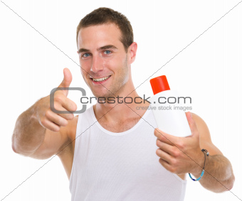 Happy young man showing sun screen creme and thumbs up