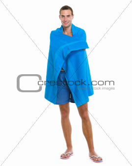 Happy young man wrapped in blue beach towel