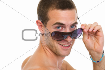 Portrait of happy young man looking out from sunglasses