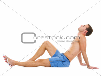 Young man sitting and sunbathing