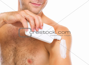 Closeup on man applying sun block creme on arm