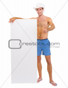Smiling man in hat showing blank billboard and thumbs up