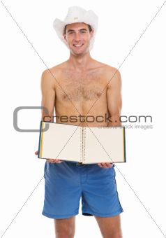 On vacation young man in shorts and beach hat showing blank photo album