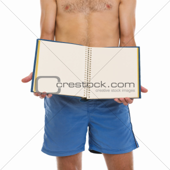 Closeup on young man in shorts showing blank photo album