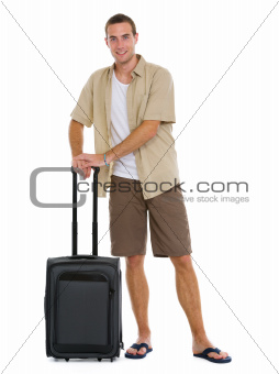 Happy tourist with wheels bag ready to vacation