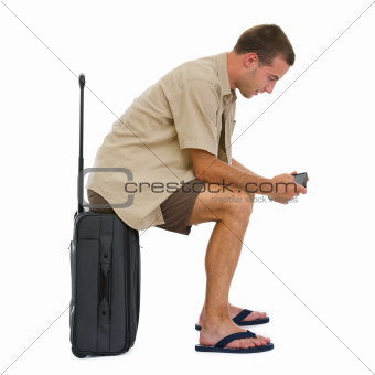 Tourist sitting on bag and checking vacation photos while waiting airplane