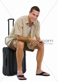 Happy tourist sitting on wheels bag and waiting for airplane