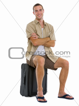 Happy tourist sitting on wheels bag