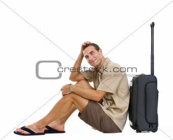 Happy tourist sitting near wheels bag and dreaming about vacation