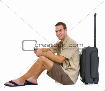 Happy tourist sitting near wheels bag