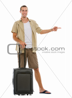 Tourist with wheels bag pointing on copy space