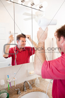 Man Blow Drying Hair in Bathroom