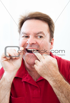Man Flossing Teeth in the Mirror