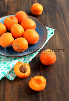 Bowl of fresh apricots on a wooden table