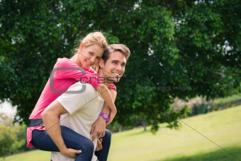 young couple running piggyback in city park