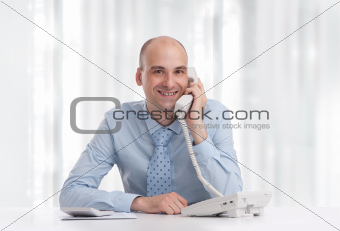 Business man at desk in office talking on phone