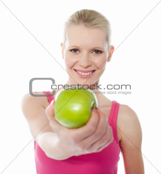 Healthy teenager offering green apple to you